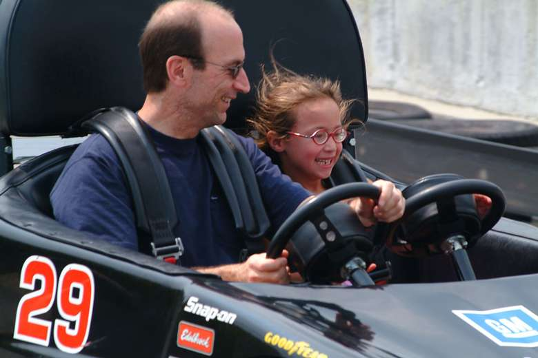 a father and daughter in a go-kart together