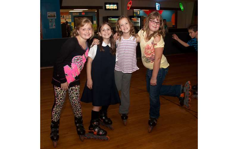 four girls posing in their roller blades