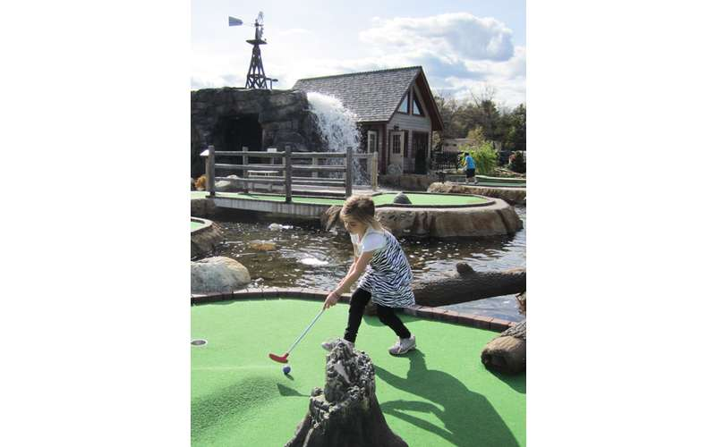 a little girl playing mini golf