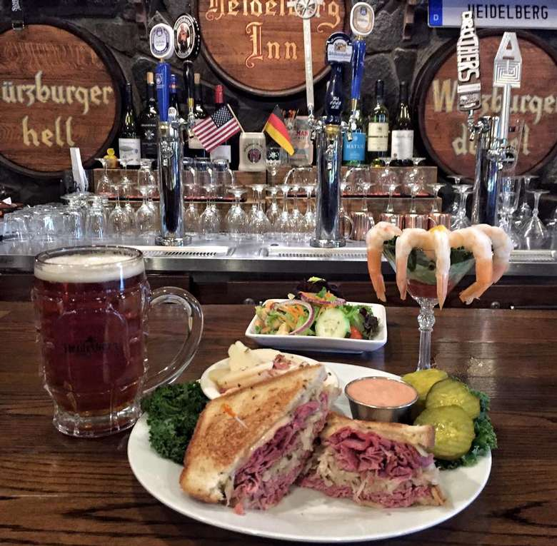 glass of beer, reuben meal on plate, and salad, and shrimp cocktail on a bar