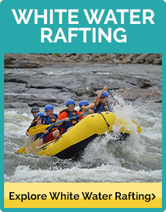 Rafters in blue helmets riding a yellow raft through the rapids