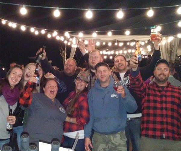 group of people in flannels with wine glasses and beers