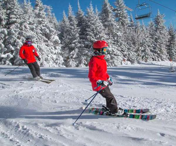 two people in red jackets skiing down Gore mountain