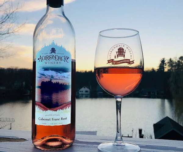 image of wine glass and wine bottle with Adirondack Winery branding