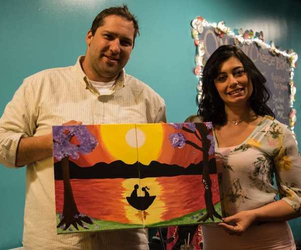 couple holding puzzle painting of a sunset and boat