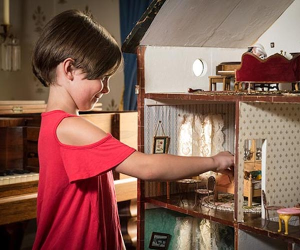 girl playing with a doll house