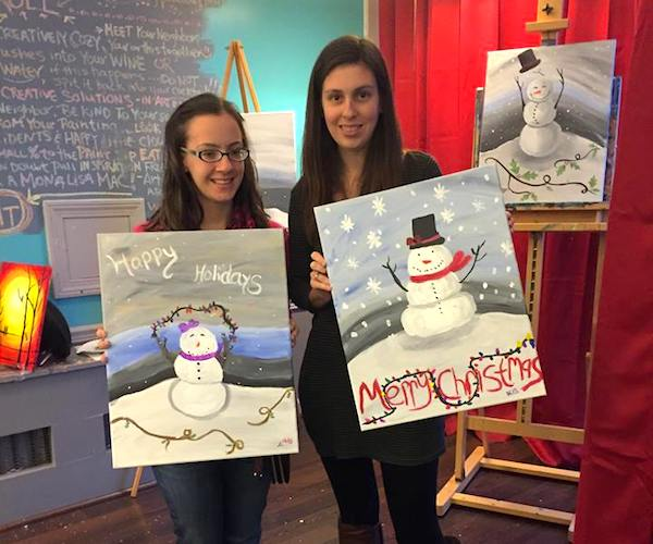 two young women holding holiday paintings