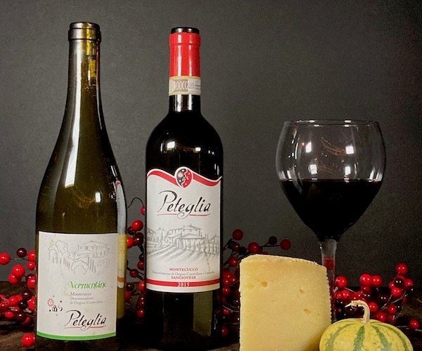 two bottles of Peteglia wine and a wheel of cheese
