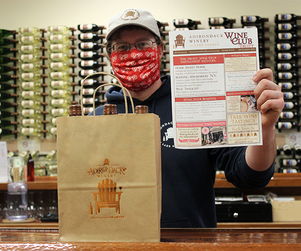 man wearing face mask holding a wine club membership application and standing in front of Adirondack Winery wine