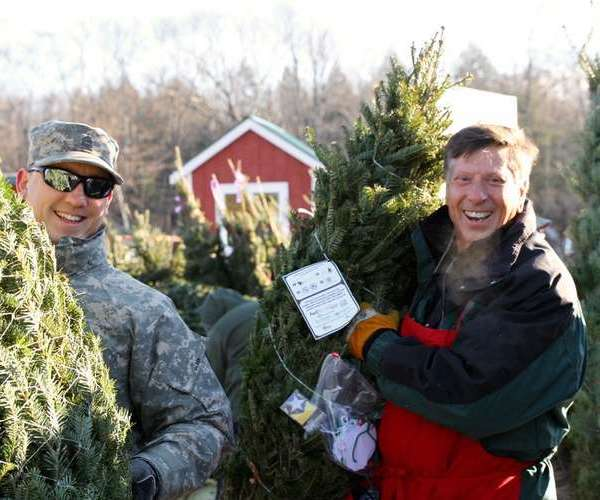 troops holding Christmas trees at Ellms Family Farms