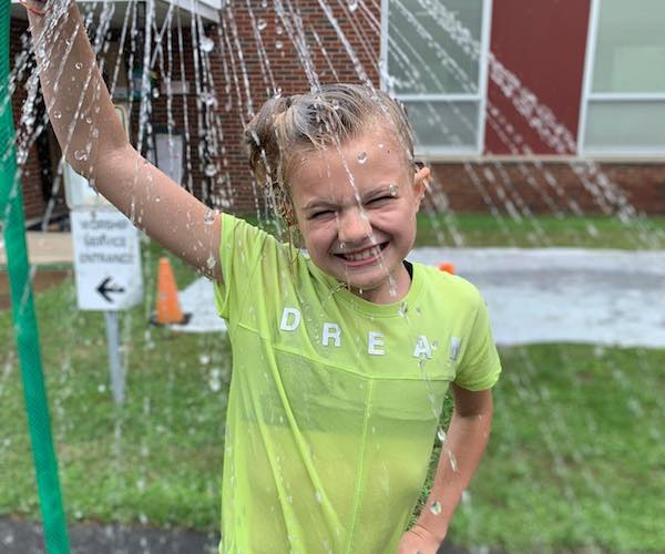 girl playing under a sprinkler and smiling