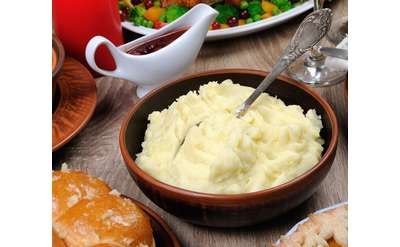 bowl of mashed potatoes, gravy and other dinner items surrounding it