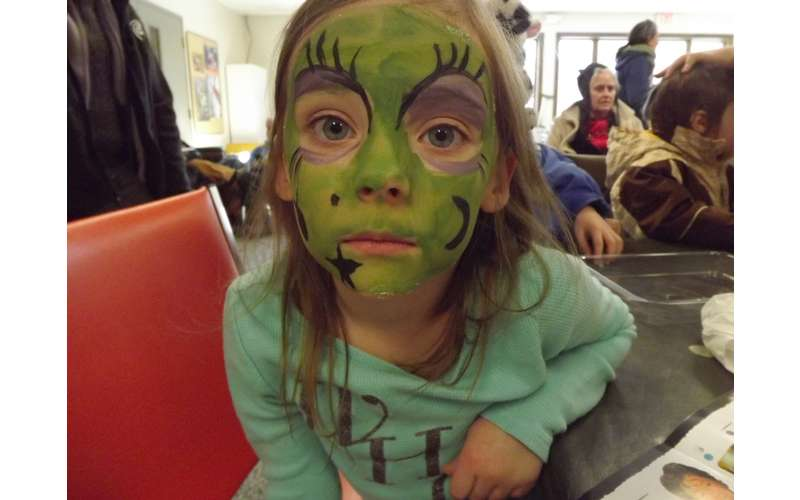 a girl with green face paint on