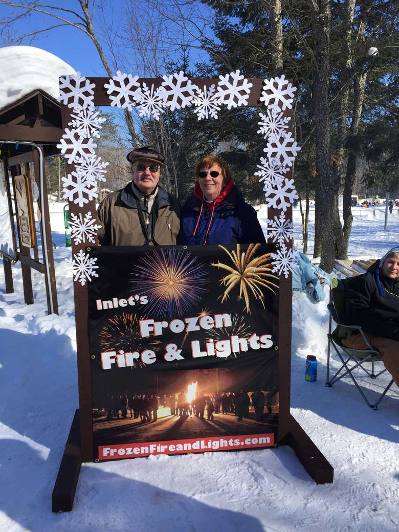two people standing being an inlet frozen fire and lights sign
