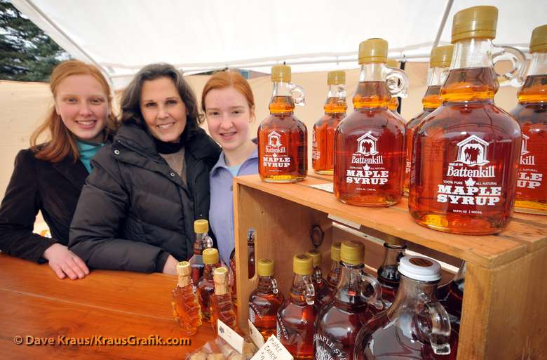 women posing next to maple syrup