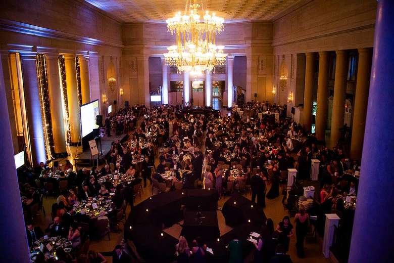 tables of people inside the hall of springs for a gala