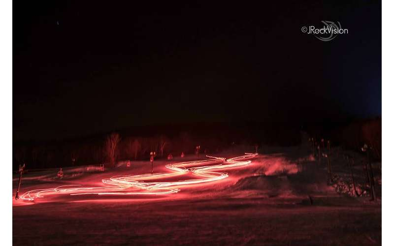 bright red lights on a snowy field in evening
