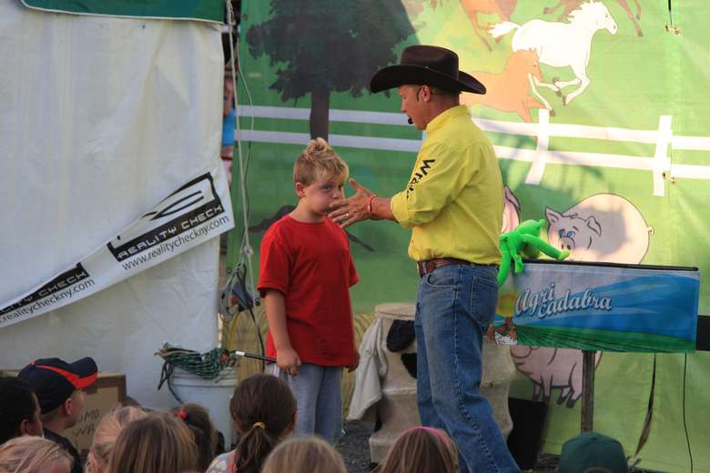 a man with a cowboy hat doing a demonstration with a little boy in a red shirt