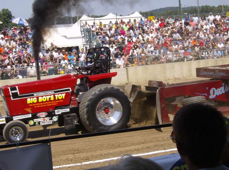 a tractor pull, crowd in the background