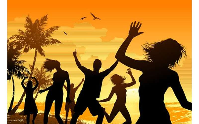 silhouettes of people partying on a tropical beach during a sunset