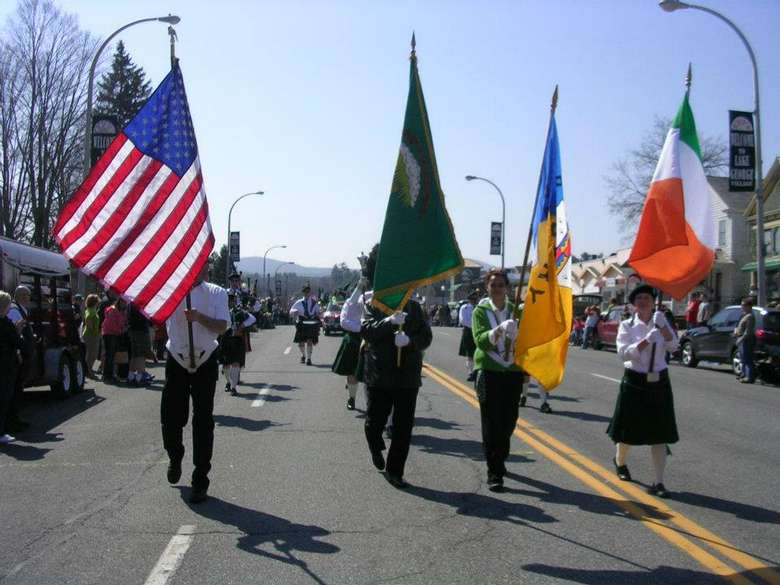 people carrying flags in st. patrick's day parade