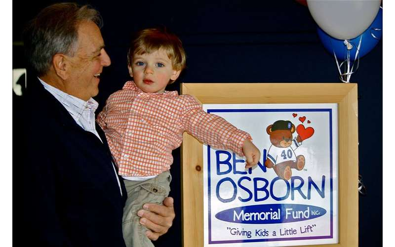 man holding up little boy in front of Ben Osborn sign
