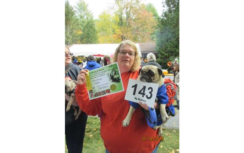 woman holding up pug and award