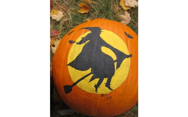 a pumpkin with a witch painted on front