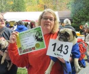 woman holding up pug and award