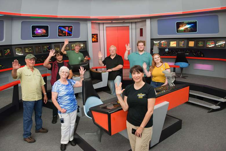 a group of star trek fans in a recreated Star Trek Enterprise control room