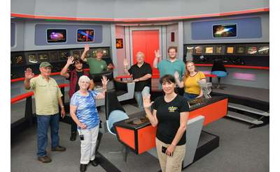 a group of star trek fans in a recreated Star Trek Enterprise control room