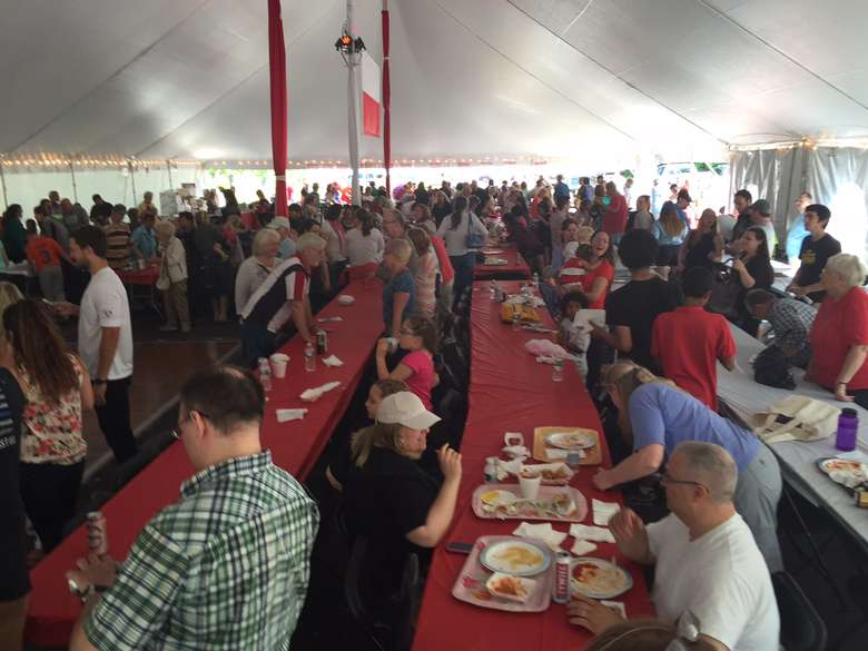 lines of tables under a big tent with people eating at them