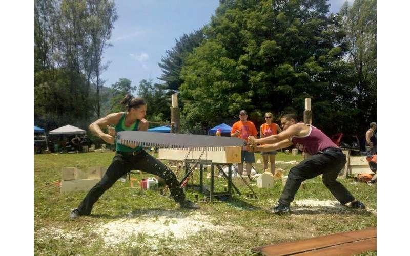 people sawing lumber