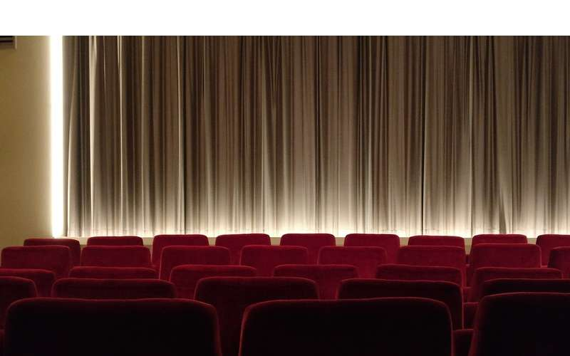 red theater seats near curtain on stage