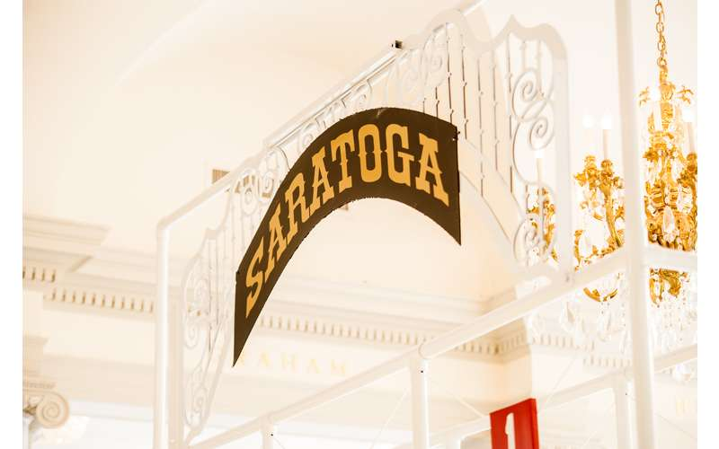 a sign that says saratoga above a gate
