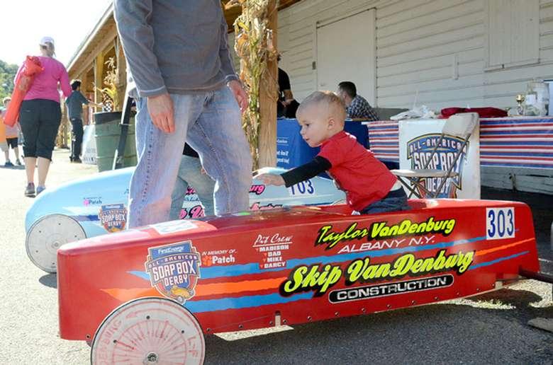 a little boy in a red kids car