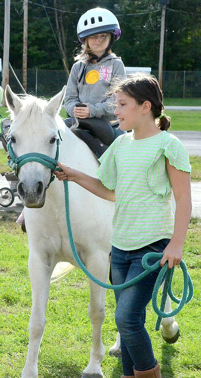 a kid riding a white pony