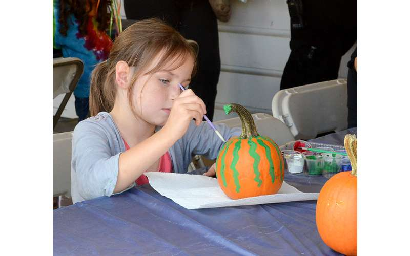a little girl painting a pumpkin