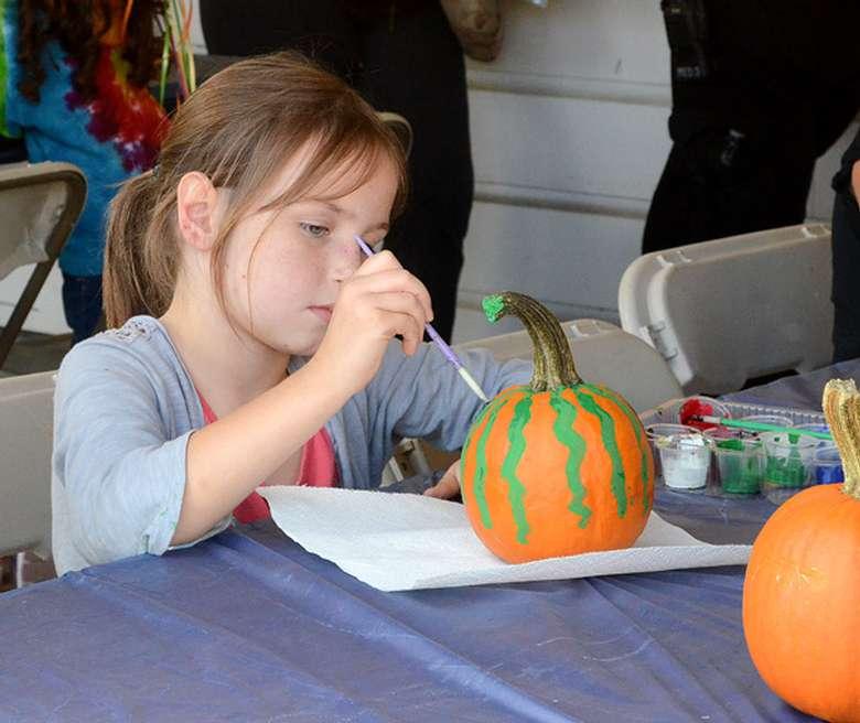 a little girl painting a pumpkin