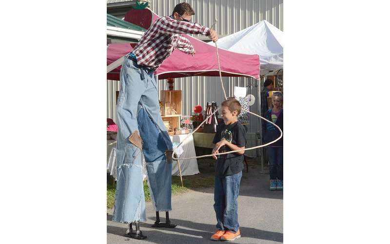 a man on stilts performing a lasso around a little boy