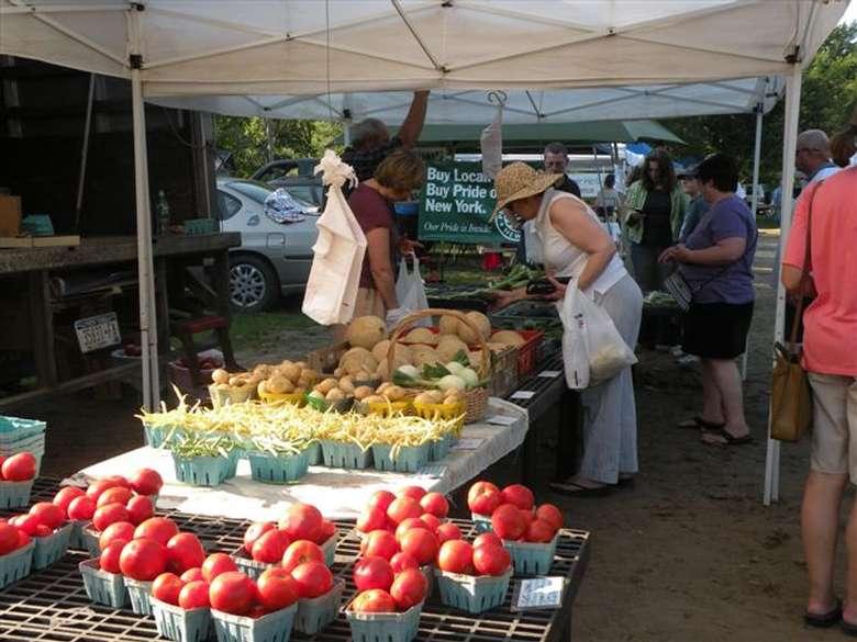 shoppers under a farmers' market tent