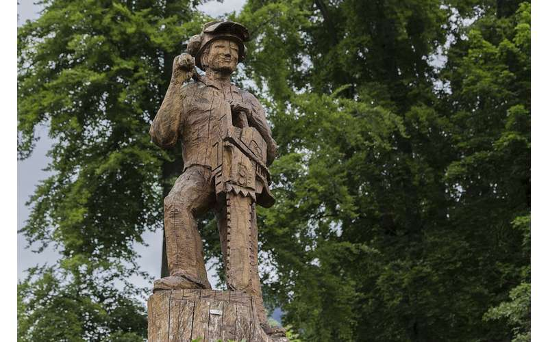 a lumberjack statue holding chainsaw made out of wood