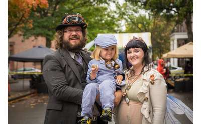 parents with little kid in steampunk clothes