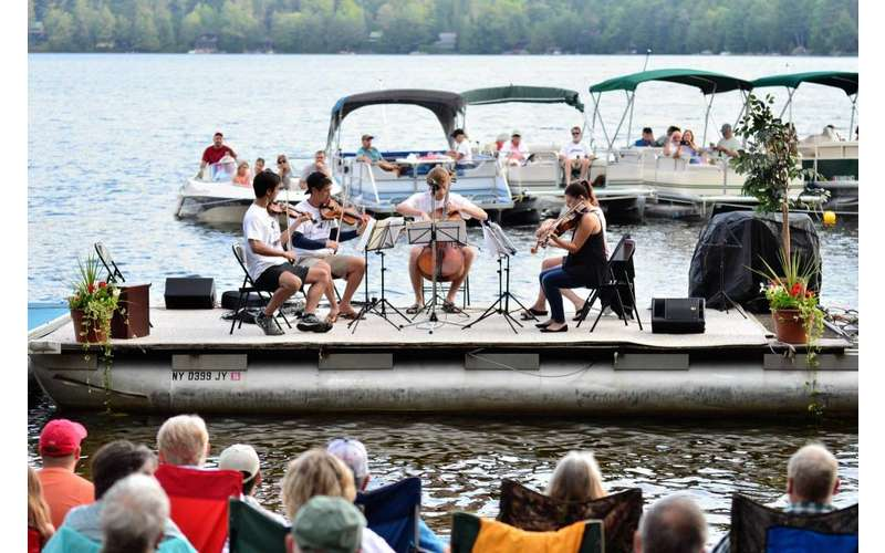 a four-piece group with string instruments perform on a boat in an open setting with other people on boats in the water watching them