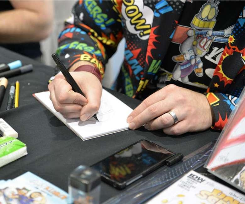 man signing something at Comic Con