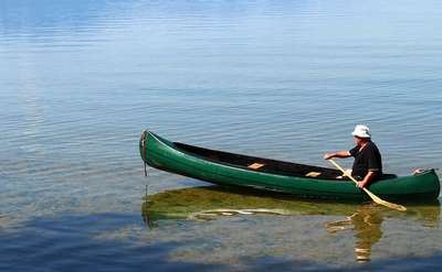 man paddling out of shallow water in a green canoe