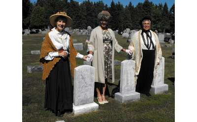three women reenactors standing near graves