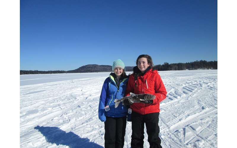 two people standing on snowy ice