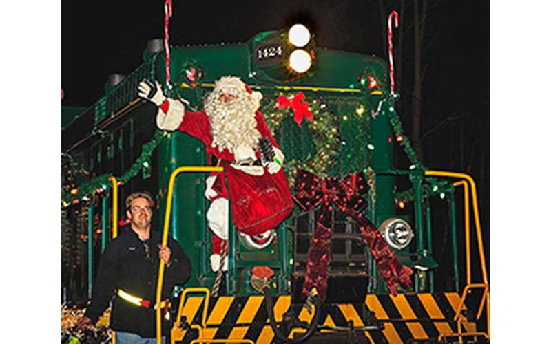 Photo of santa in front of a train