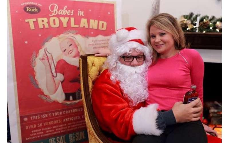 blonde woman on Santa's lap, he has a bottle of liquor